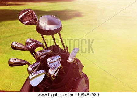 Golf bag with clubs on green field, close up