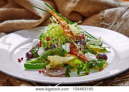Fresh spring salad with feta cheese, red onion in white bowl.