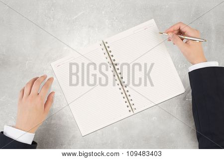 Businessman hand with pen writting in blank notepad