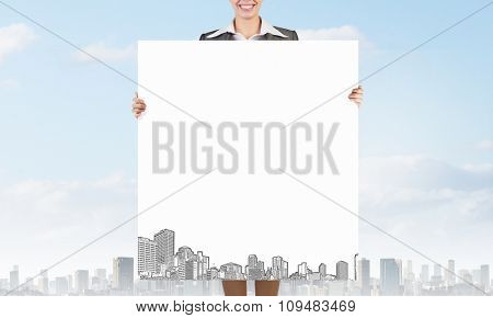 Young businesswoman showing white banner with construction sketches