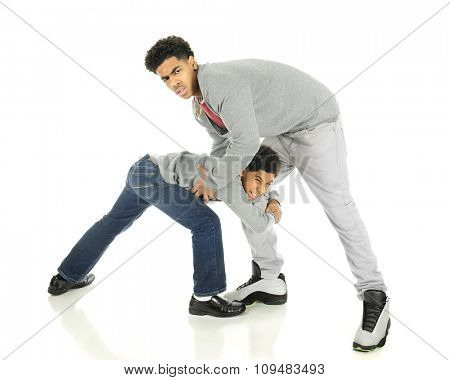 A very tall teenage man wrestling with his elementary brother.  On a white background.