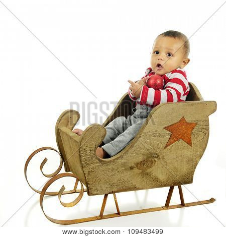 An adorable baby boy happily sitting in an old wooden sleigh holding a red Christmas ornament.  On a white background.