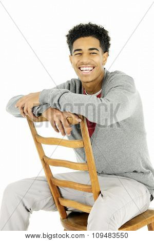 A happy older teen sitting backwards on a ladder-back chair.  On a white background.
