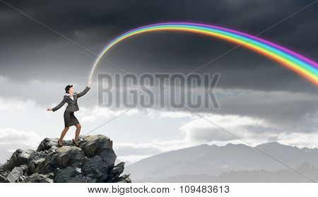 Young businesswoman in bowler hat and colorful rainbow in hand