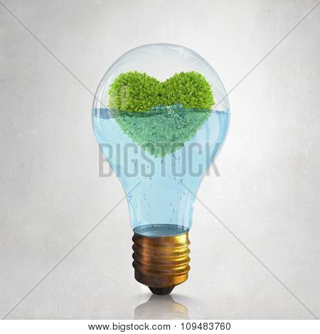 Glass lightbulb with water and love shaped green tree inside