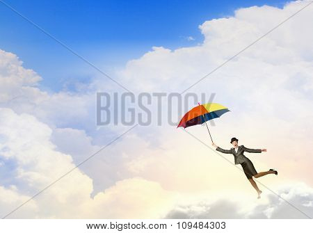 Young businesswoman in suit and hat with colorful umbrella