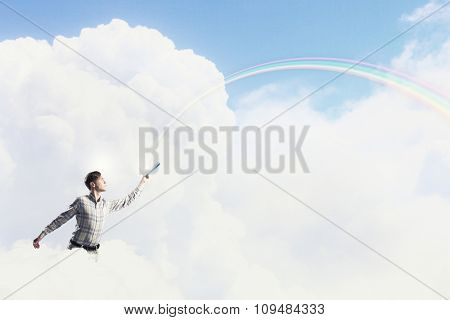 Young handsome man on sky background reaching hand with book