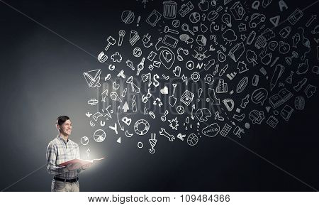 Young man with book in hands and light out of pages