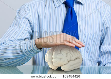 Hands of man holding with care human brain