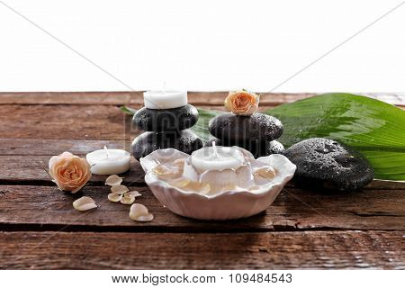 Spa composition of stones, candles and a rose, isolated on white