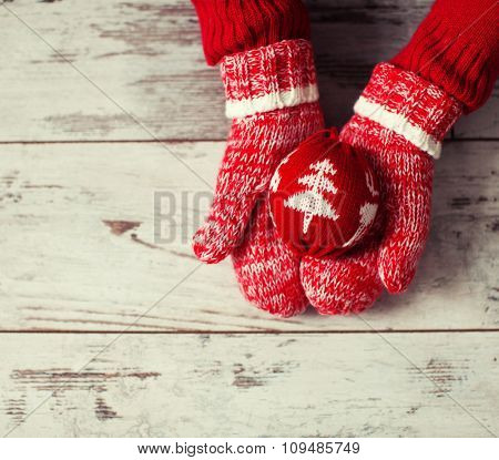 Mitten with christmas ball on wood floor. Winter decoration