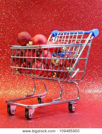 Shopping Cart With Red Decorative Christmas Balls And Glitter Background