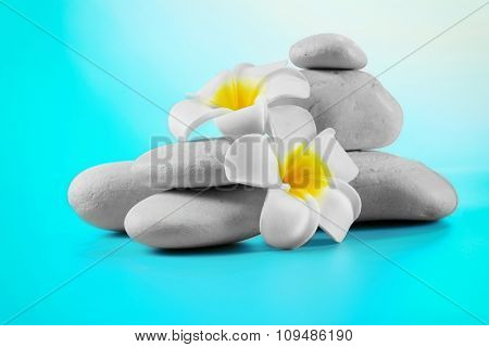 Spa stones and flowers on blue background