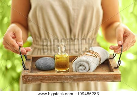 Female hands with tray of spa products, at spa salon