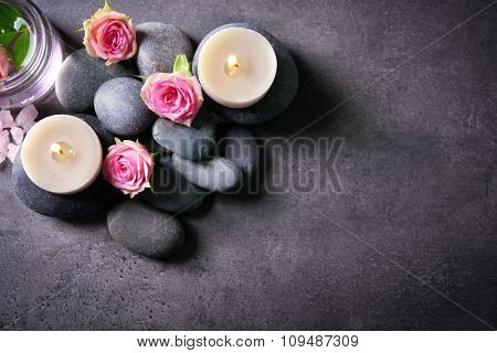 Spa composition of candles,  stones and flowers, on grey background