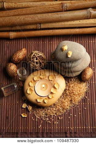 Decorated composition with candles and pebbles on bamboo mat