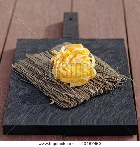 Two types of pasta on an old cutting board