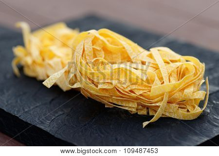 Egg tagliatelle on wooden plank, limited focus depth