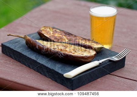 Grilled eggplant and a glass of beer on table