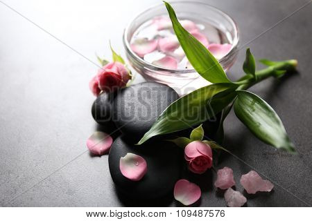 Spa composition of stones, flowers and petals, on grey background