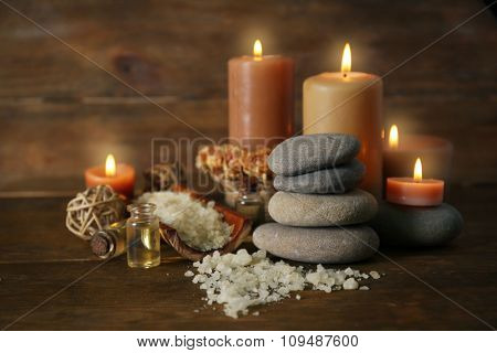 Beautiful relax composition with candles and pebbles on wooden background