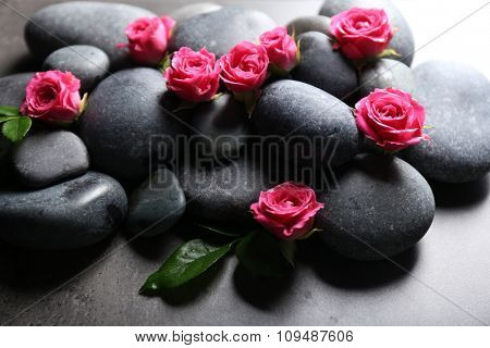 Spa composition of stones and flowers, on grey background