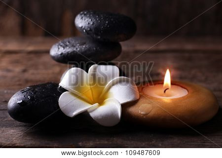 Relaxing set of fragipani flower, pebbles and alight candle on wooden background