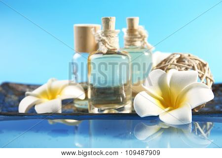 Beautiful composition of aroma oil and flowers on water against blue background