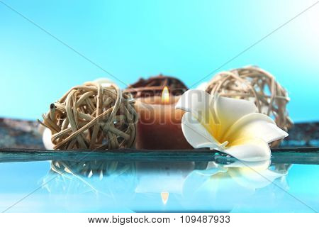 Beautiful composition of candles, decorative wicker balls and flowers on water against blue background