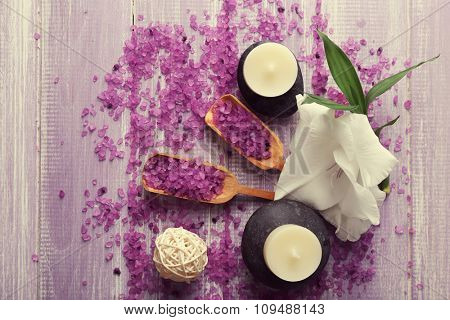 Spa composition of candles, stones, sea salt and flower on purple wooden background