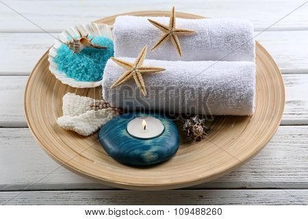 Marine style spa composition in a bowl on wooden background