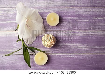 Spa composition of candles, oil and white flower on purple wooden background