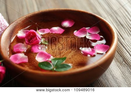 Spa composition of flowers in water, on wooden background