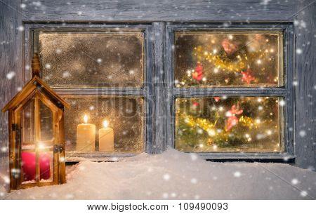 Lantern on window sill in winter mood. Blur christmas tree inside