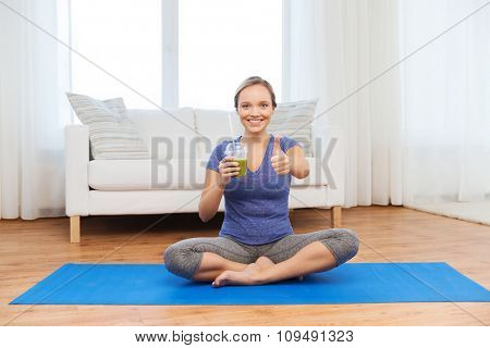 fitness, sport, people, diet and healthy lifestyle concept - happy woman with cup of smoothie sitting on mat at home and showing thumbs up