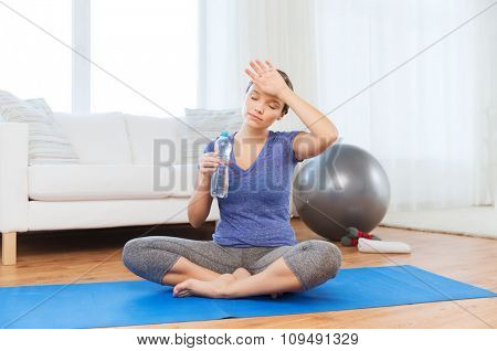 fitness, sport, people and healthy lifestyle concept - tired woman with bottle of water after exercising on mat at home