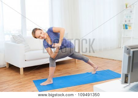 fitness, sport, people and healthy lifestyle concept - woman making yoga low angle lunge pose on mat and watching tv lesson