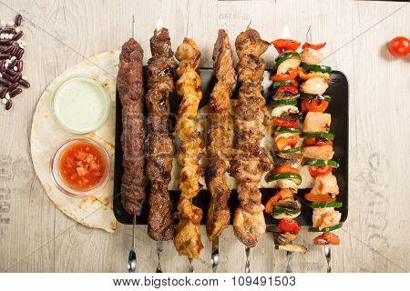 set shashlik. kebab skewer, black rectangular plate. sauce and onions