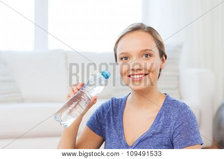 people and healthy lifestyle concept - happy woman with bottle of water at home