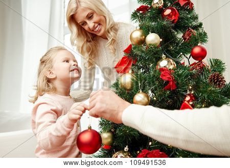 family, x-mas, winter holidays and people concept - happy mother, father and little daughter decorating christmas tree at home