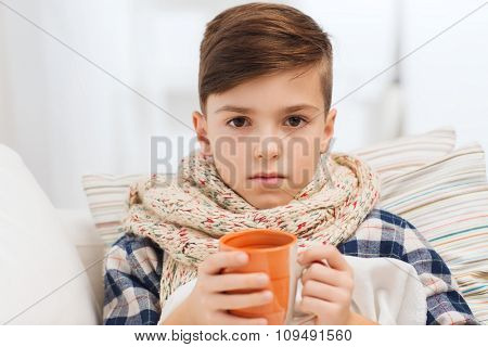 childhood, healthcare, people and medicine concept - ill boy with flu lying in bed and drinking tea at home