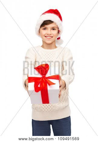 holidays, presents, christmas, childhood and people concept - smiling happy boy in santa hat with gift box