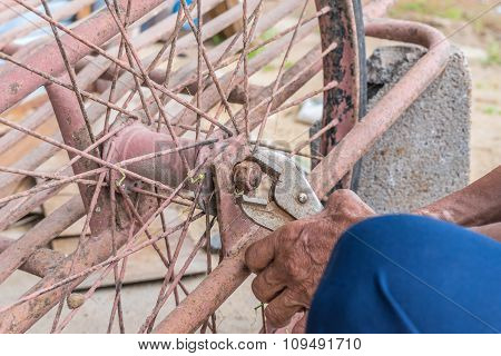Close-up Of Person Hands Repairs Wheel Bicycle With Pliers