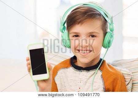 leisure, children, technology, advertisement and people concept - smiling boy with smartphone and headphones listening to music at home