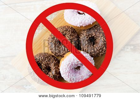 fast food, low carb diet, fattening and unhealthy eating concept - close up of glazed donuts on wooden board behind no symbol or circle-backslash prohibition sign