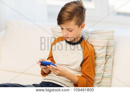 leisure, children, technology, internet addiction and people concept - boy with smartphone texting message or playing game at home