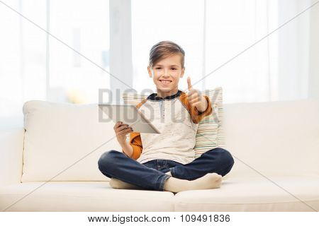 leisure, children, technology and people concept - smiling boy with tablet pc computer showing thumbs up at home