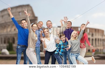 family, travel, tourism and people concept - group of happy men, women and boy having fun and waving hands over coliseum background