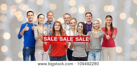 gesture, shopping and people concept - group of smiling men and women showing thumbs up and holding red sale sign or banner over holidays lights background