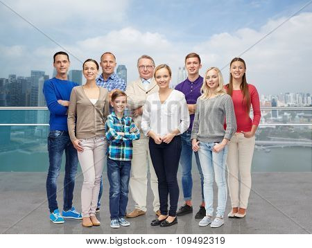 family, travel, tourism, generation and people concept - group of smiling men and women over singapore city background